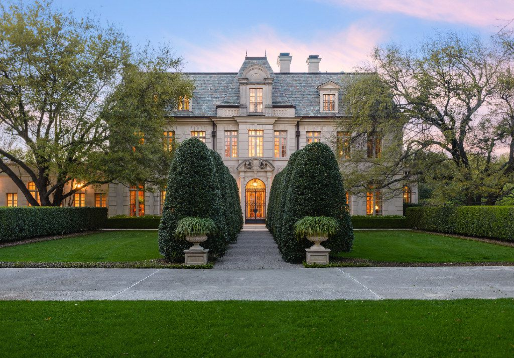 Two rows of holly trees line the formal entrance of the home of Bobby Haas. The Preston Hollow estate is on the market for $27.5 million.