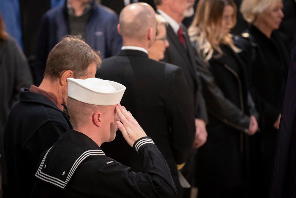 A sailor salutes the flag-draped casket of President George H.W. Bush as he lies in the Rotunda of the U.S. Capitol on Tuesday, Dec. 4, 2018, in Washington.