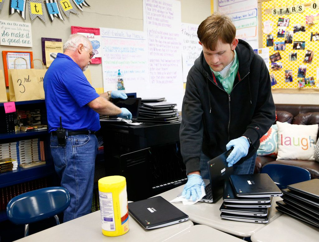 David Withrow (left) and Andrew Wilson with the IT department clean laptops in the classrooms of Sunnyvale Middle School The school district has been hit by flu and is shut down today and tomorrow (Nathan Hunsinger/The Dallas Morning News)