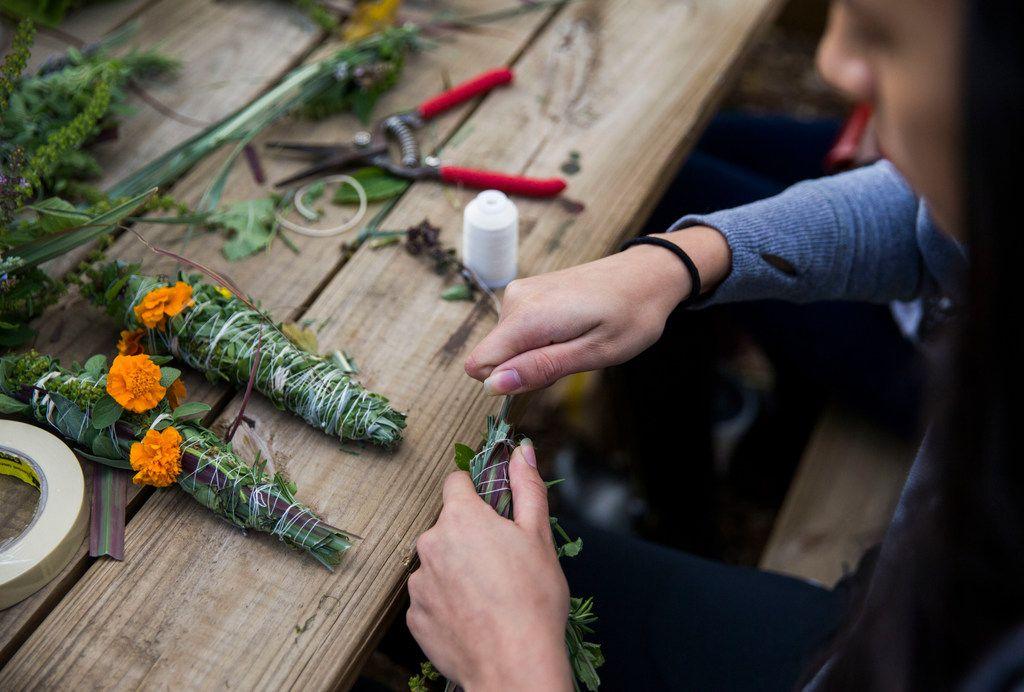 Intern Kimberly Berrios, 15, makes an herb bundle.