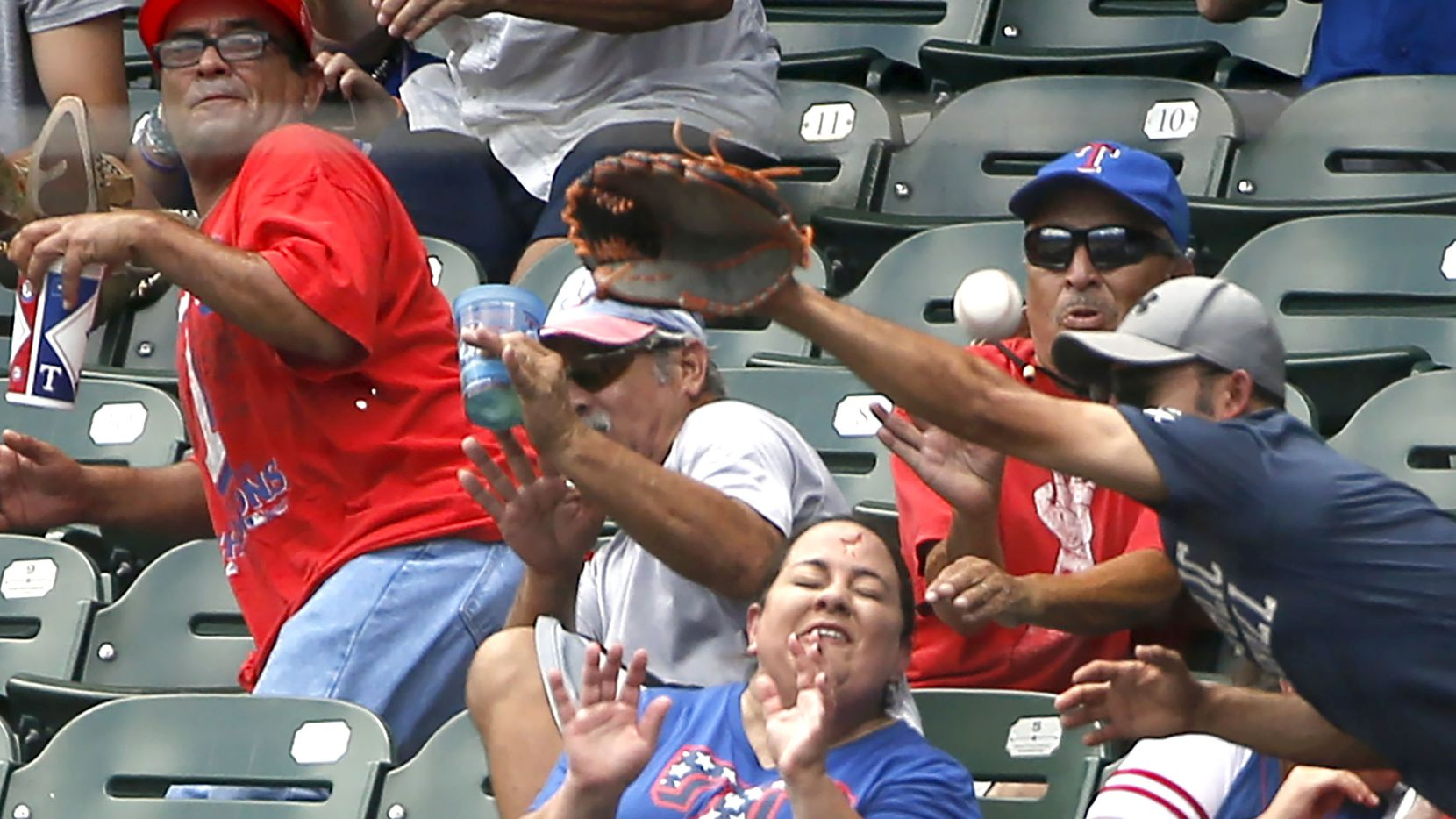 ARLINGTON, TX - AUGUST 4: A fan reacts after being stuck in the forehead by a foul ball off the bat of Willie Calhoun #5 of the Texas Rangers as the Rangers play the Detroit Tigers during the first inning at Globe Life Park in Arlington on August 4, 2019 in Arlington, Texas. (Photo by Ron Jenkins/Getty Images)