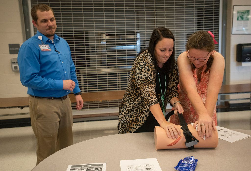 UT Health East Texas paramedic Tracy Sims oversees Winona ISD elementary school counselor Kristin Tillman and life skills aide Melisa Albright during Stop the Bleed tourniquet training and Hands Only CPR training for all Winona ISD employees at the school in Winona on Wednesday Aug 7, 2019.