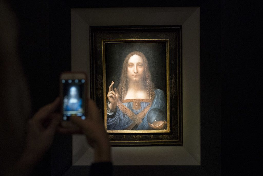 A visitor takes a photo of the painting Salvator Mundi by Leonardo da Vinci at Christie's New York Auction House. The coveted painting was sold at auction for $450.3 million Wednesday night.