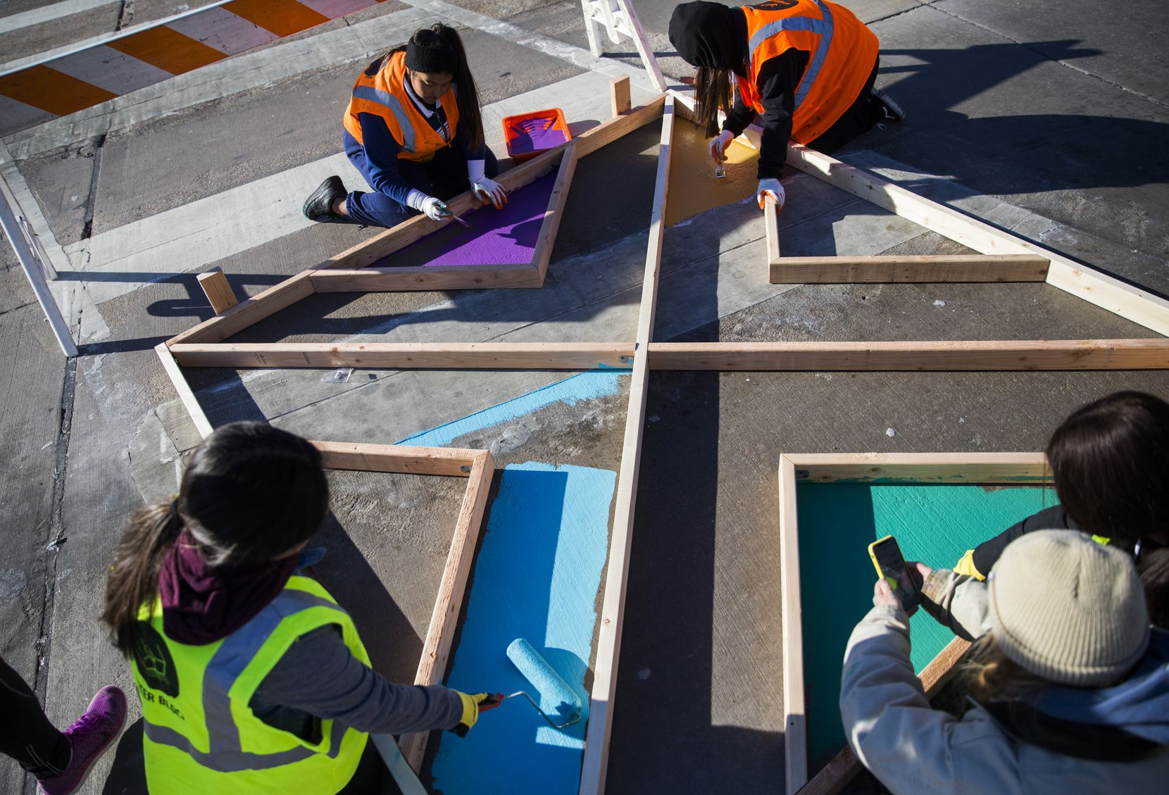 Yamilet Chavez, 13, (clockwise, from bottom left), Melanie Aguillar, 13, (top left), Sherlyn Hernandez, 13, (top right), and Sharely Vences, 13, (right), paint a crosswalk as part of Better Block's effort to transform the Five Points intersection on Thursday.