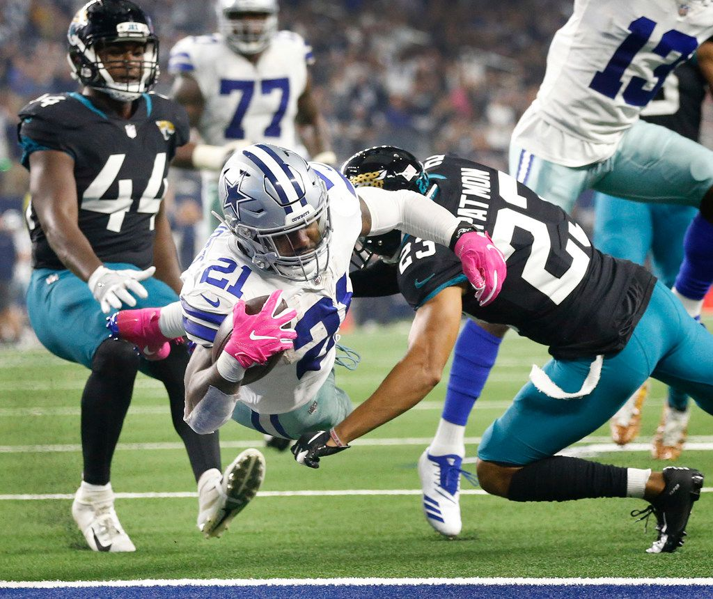 FILE - Cowboys running back Ezekiel Elliott (21) dives across the goal line for a touchdown as he's hit by Jaguars defensive back Tyler Patmon (23) during a game at AT&T Stadium in Arlington on Sunday, Oct. 14, 2018. (Tom Fox/The Dallas Morning News)