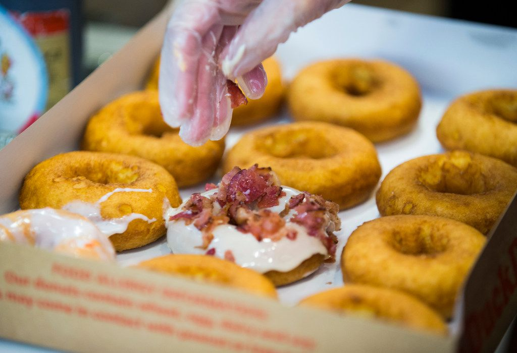 Duck Donuts starts with just one option: a vanilla-cake doughnut. Then, customers choose their own doughnut coating, topping and drizzle. (Pictured here: maple icing with bacon on top)