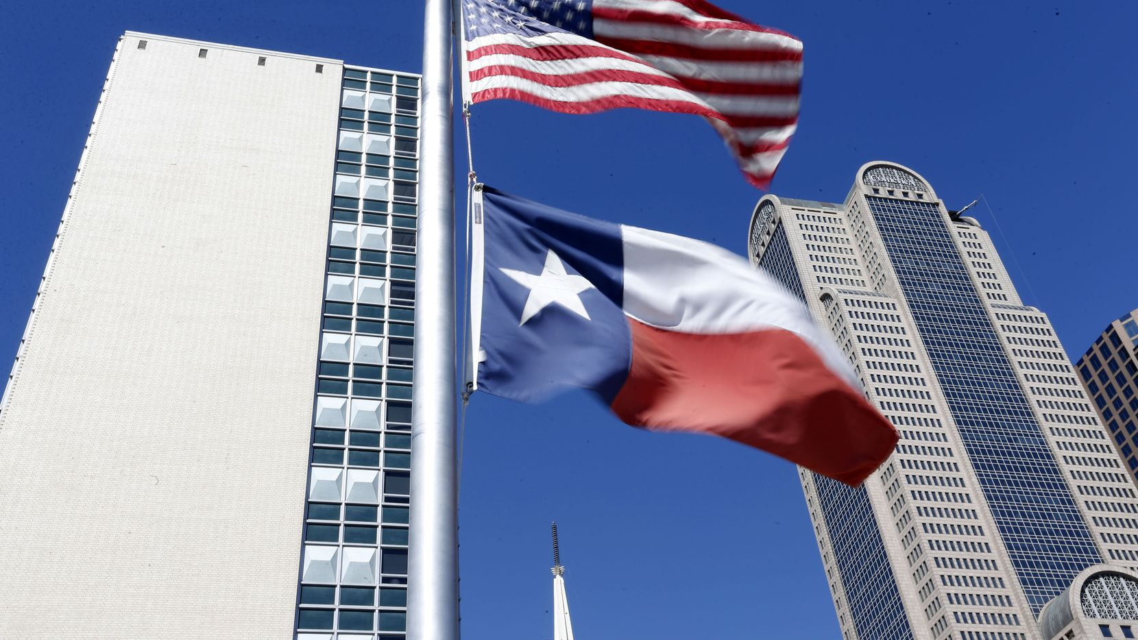 The U.S. and Texas flags fly at half staff above The Dallas Morning News building.