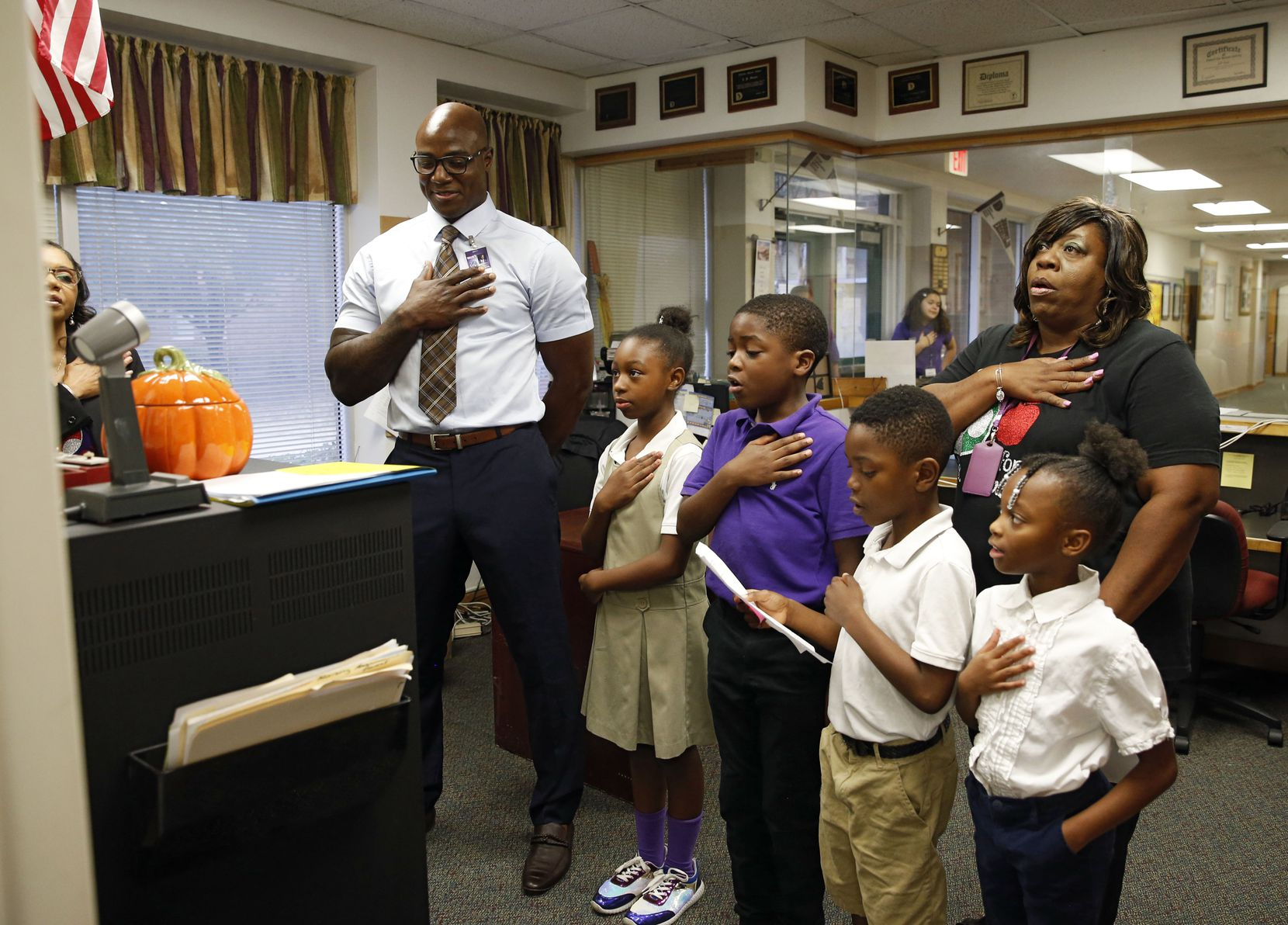 Ware recites the Pledge of Allegiance with Howard (left), Starks students Markayla Green, D'Coreyian Wilson, Sim'meon Williams and Ivyunna Oatman, and fourth-grade science teacher Stephanie Simon during morning announcements.