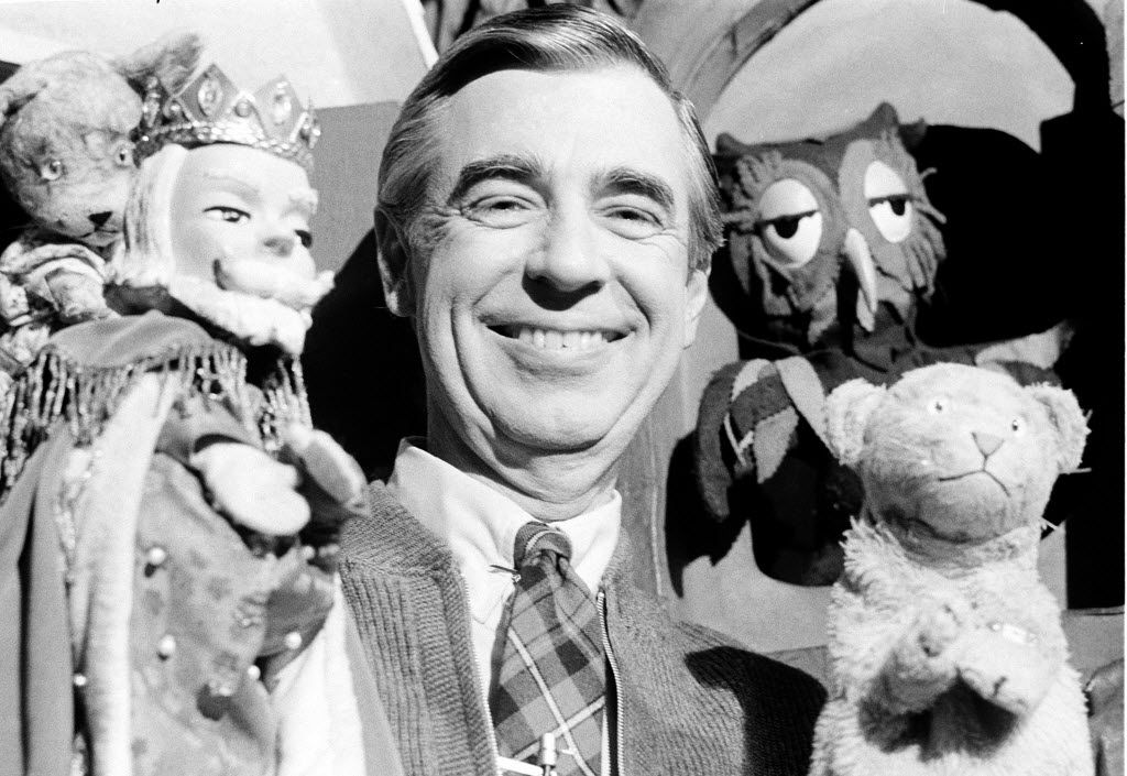 This Jan. 4, 1984 file photo shows Fred Rogers, star of Public Television's Mister Rogers' Neighborhood, as he rehearses with some of his puppet friends in Pittsburgh, Pa.  In 1968, one year before Sesame Street premiered, Mr. Rogers' Neighborhood broke ground by addressing children's interests and concerns through electronic media. He merged documentary-style segments about real people with scenes in a sitcom-like living room and excursions into a fantasy world populated by puppets. And yet he was wary of using every technological tool at his disposal.   (AP Photo/Gene J. Puskar, file)