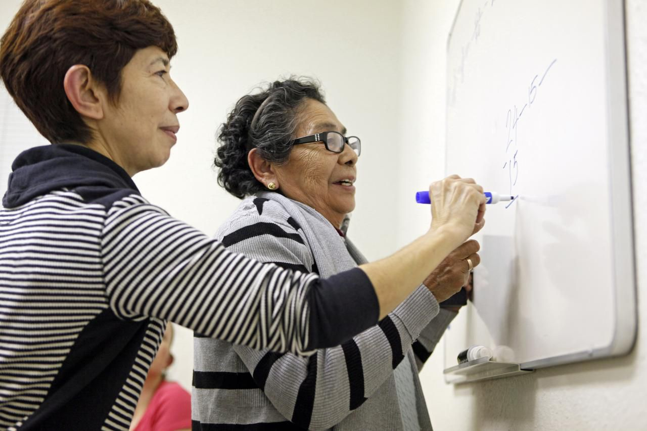 La maestra de matemáticas Hortensia Chonguin (izq.) ayuda a Ángela Acevedo, de 80 años, a resolver un problema de matemáticas durante una clase para adultos en la Plaza Comunitaria Dallas Norte. (ESPECIAL PARA AL DÍA/BEN TORRES)