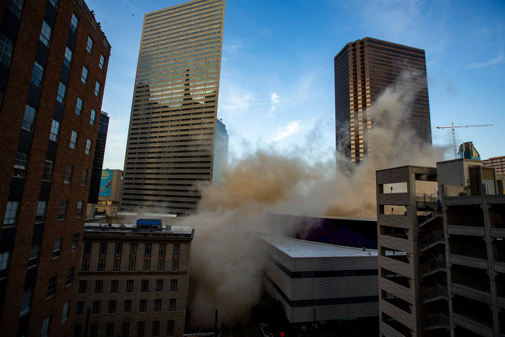 People take pictures of a building located at 505 north Ervay St. in downtown Dallas as it is brought down in a controlled implosion on Saturday, June 29, 2019. (Shaban Athuman/Staff Photographer)