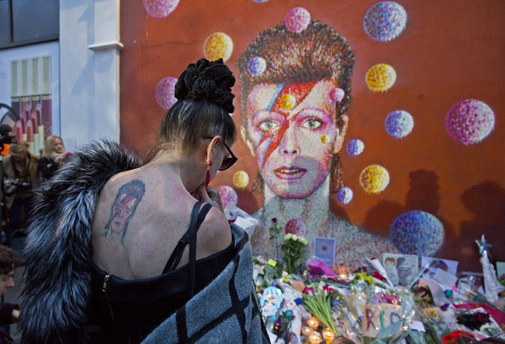 """A woman with a tatoo of David Bowie reacts as she pays her respects in front of the British singer, painted by Australian street artist James Cochran, aka Jimmy C, following the announcement of Bowie's death, in Brixton, south London, on January 11, 2016. British music icon David Bowie died of cancer at the age of 69, drawing an outpouring of tributes for the innovative star famed for groundbreaking hits like """"Ziggy Stardust"""" and his theatrical shape-shifting style."""
