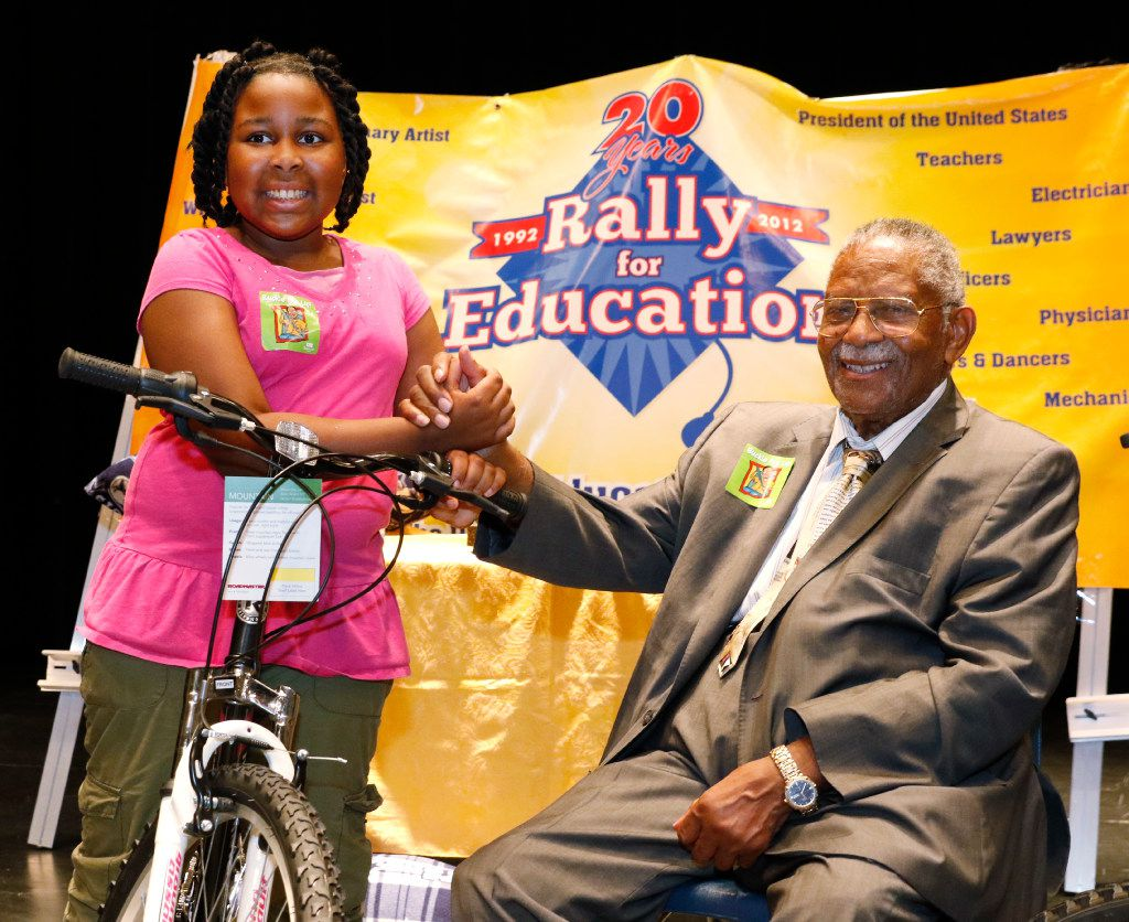 """Eryn Tucker-Green, 10, poses with Judge L. Clifford Davis after winning first place in competitive writing contest for her essay, """"Bullying and What You Can Do To Stop It."""" She also won a bicycle in a raffle at the 25th Annual Rally for Education at Jean McClung Middle School in Fort Worth on June 15, 2017."""