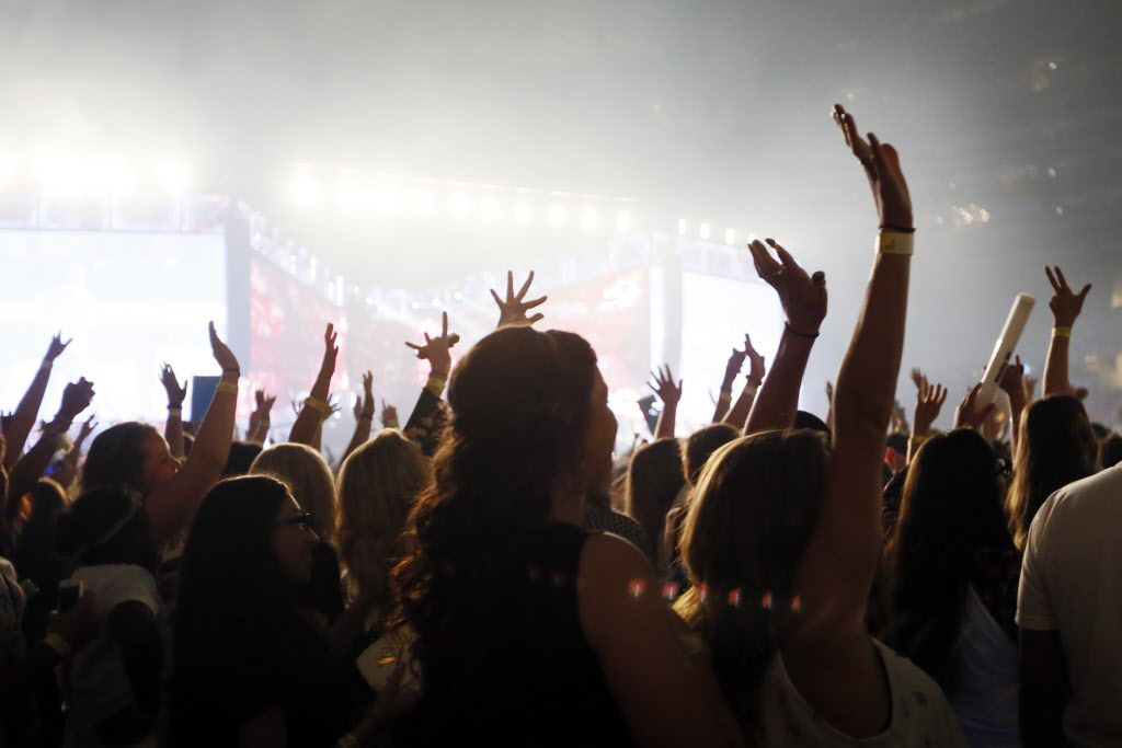 Fans raise their hands during One Direction performs at AT&T Stadium in Arlington, TX August 24, 2014.