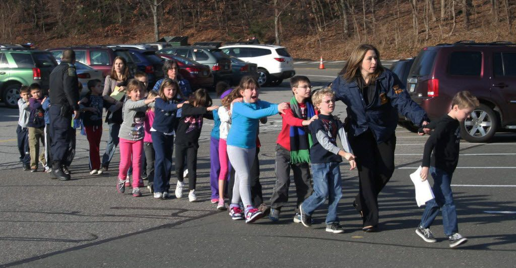 In this file photo, Connecticut State Police lead a line of children from the Sandy Hook Elementary School in Newtown, Conn. on Dec. 14, 2012, after a shooting at the school.