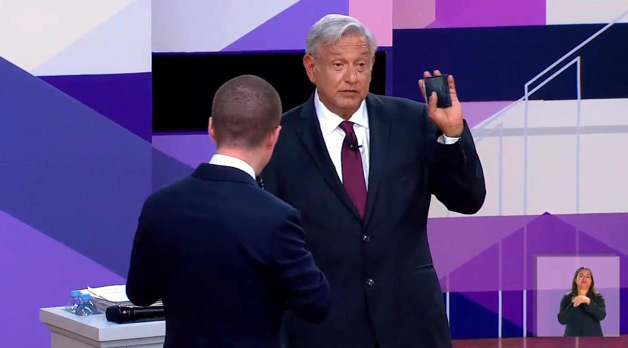 El candidado Andrés Manuel López Obrador levanta su cartera cuando se le acerca el candidato Ricardo Anaya durante el debate presidencial.(AGENCIA REFORMA)