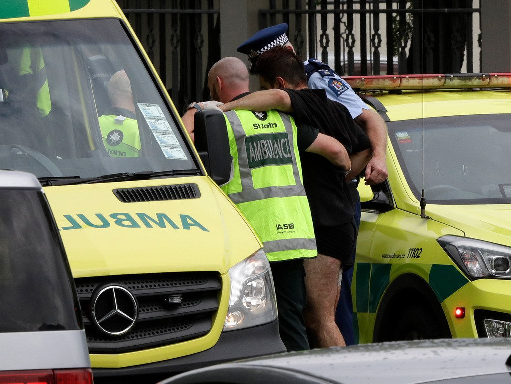 Police and ambulance staff help a wounded man from outside a mosque in central Christchurch, New Zealand.