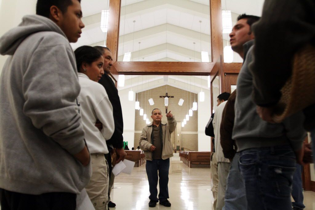 Father Edmundo Paredes spoke with church ushers during last-minute preparations for St. Cecilia's new church dedication Mass and ceremony in November 2011.