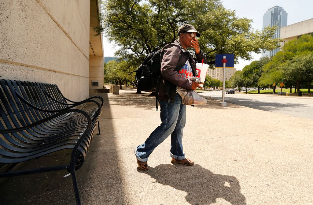 With her cup of water and peanut butter crackers in one hand and her belongings on her back, Tara Jackson of South Dallas leaves the disappearing shade near the Kay Bailey Hutchison Convention Center for the comforts of the Central Library in downtown Dallas on July 18.