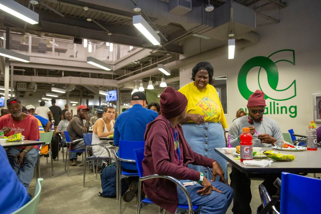 OurCalling volunteer Pat Scott (center) speaks with the unsheltered homeless during a Monday Night Football party drawing over 150 to the center in Dallas on Nov. 5, 2018.
