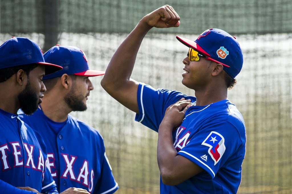 Texas Rangers pitcher Jose Leclerc flexes for fellow pitchers Yohander Mendez (left) and Martin Perez during a spring training workout at the team's training facility on Saturday, Feb. 27, 2016, in Surprise, Ariz. (Smiley N. Pool/The Dallas Morning News)