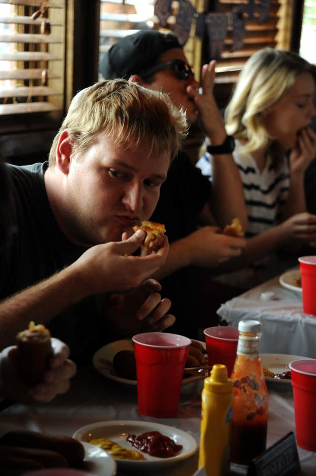 Second place winner Ryan Berry eats corn dogs at the 7th annual Brass Knuckles Corn Dog Beatdown at The Libertine Bar on July 4, 2015.