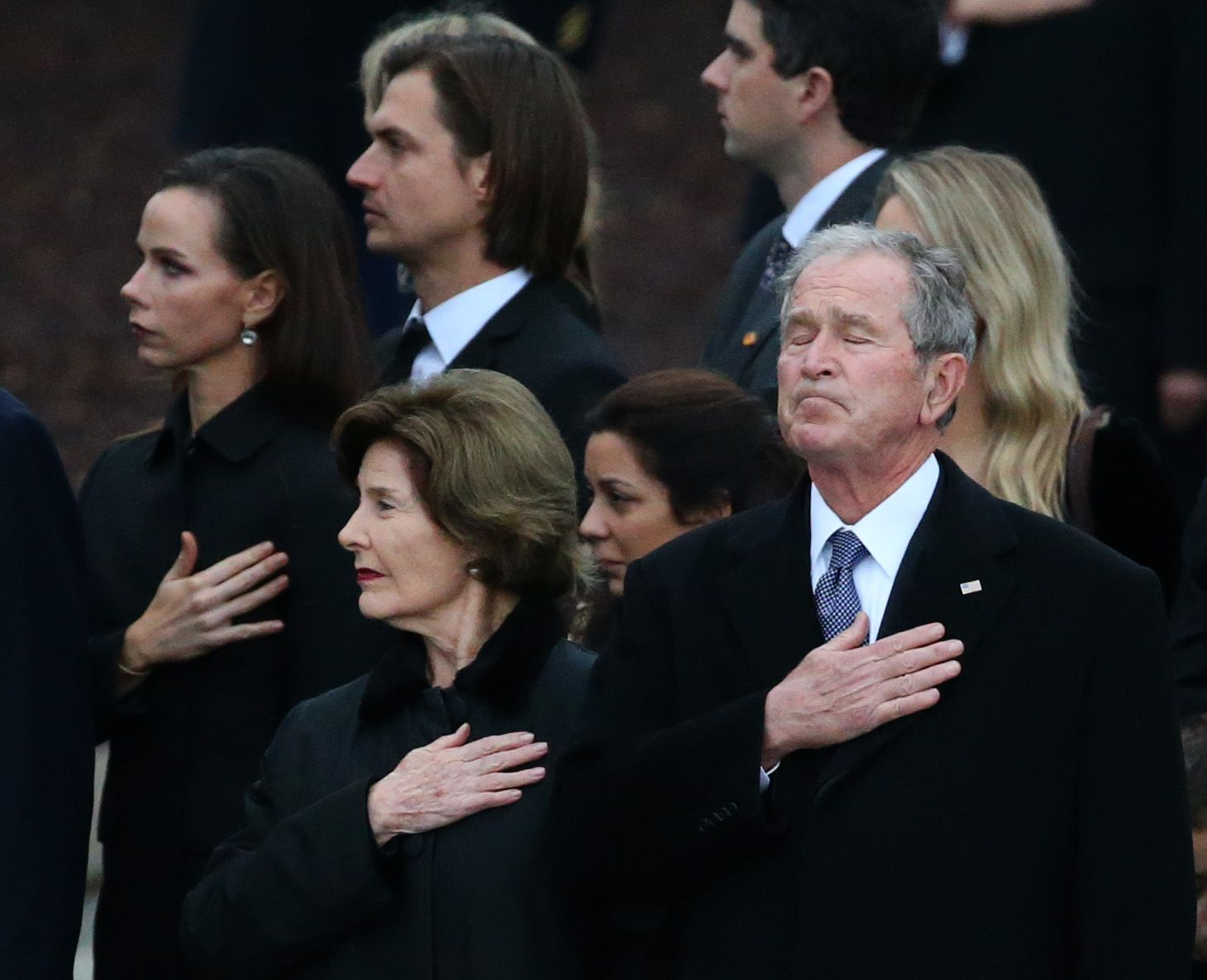 Former President George W. Bush reacts alongside his wife Laura Bush as the flag-draped casket of his father former President George H.W. Bush is carried by a joint services honor guard from the funeral train pulled by a custom-painted Union Pacific Locomotive 4141 to his final resting place at the George H.W. Bush Presidential Library Center on Texas A&M University campus in College Station, Texas on Thursday, Dec. 6, 2018. (Rose Baca/The Dallas Morning News)