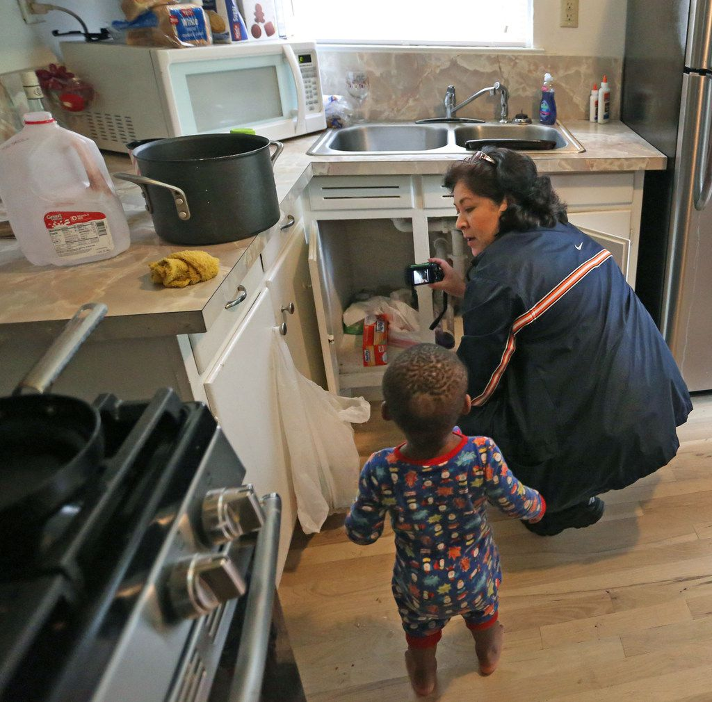 London Armstead watches as city of Dallas code inspector Diana Conde checks to see if a repair was done at a single-family rental in North Dallas on Nov. 1.