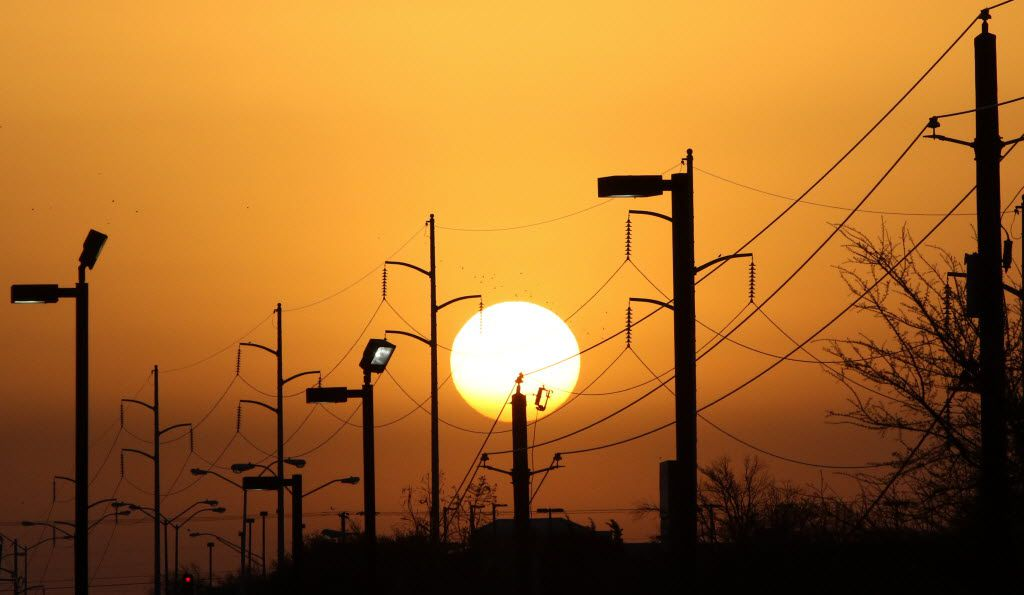 Overhead power lines and light poles are silhouetted as the morning sun rises over Camp Wisdom Road in Dallas.