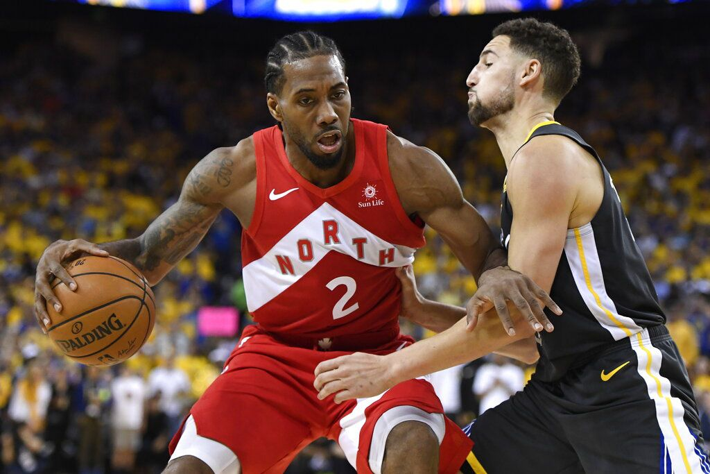 Kawhi Leonard, alero de los Raptors de Toronto, controla el balón delante de Klay Thompson, de los Warriors de Golden State, el jueves 13 de junio de 2019, en el sexto partido de la Final de la NBA (Frank Gunn/The Canadian Press via AP)