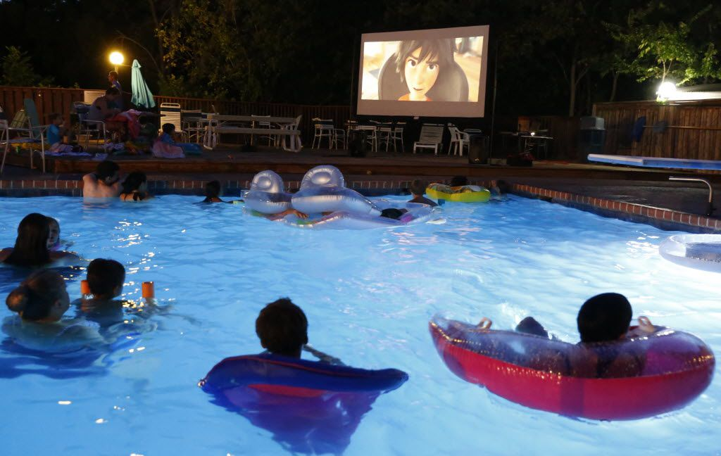 Swimmers gather around the screen at Movie Night at the Texas Pool in Plano on Aug. 15, 2015. The feature was Big Hero 6.