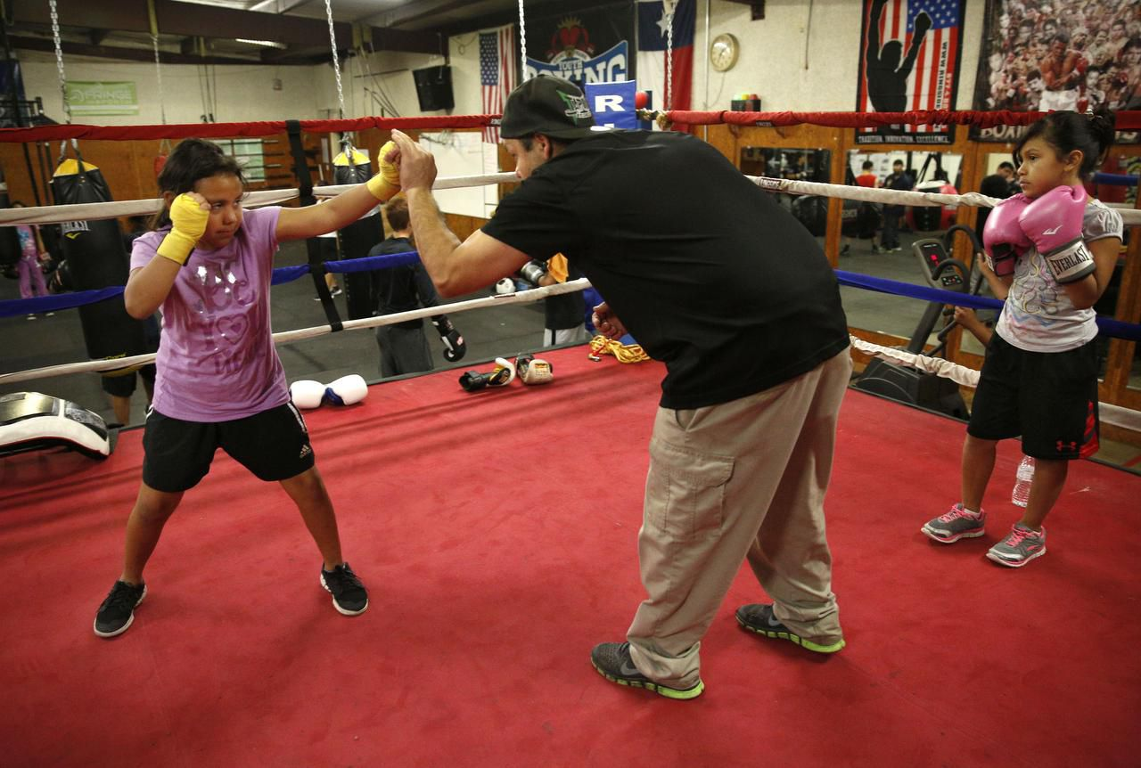 Jose Peres coaches  his daughter Angela Peres, 9, while Emily Giron, also 9, waits her turn at the youth boxing gym at Houston Elementary in Grand Prairie. The boxing program was started by the Grand Prairie Police Department.