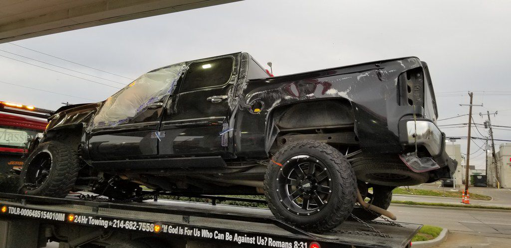 A damaged truck sits on a tow truck after a wreck in the 3200 block of LBJ Freeway.