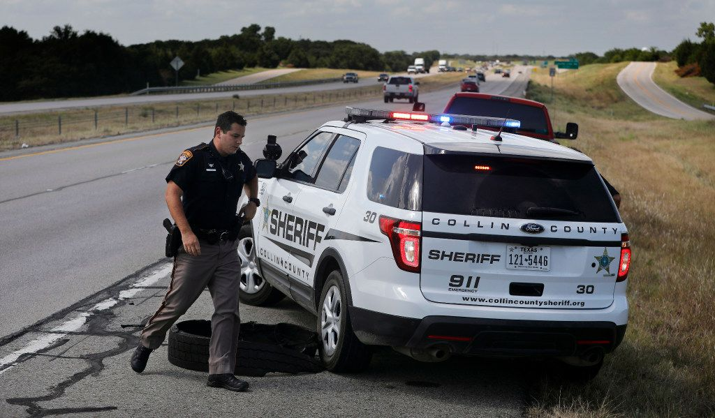 Collin County Sheriff's Deputy Rodney Tackett steps around his vehicle as he and his partner Kelly Reynolds made a stop on U.S. Highway 75 in Collin County on Tuesday.