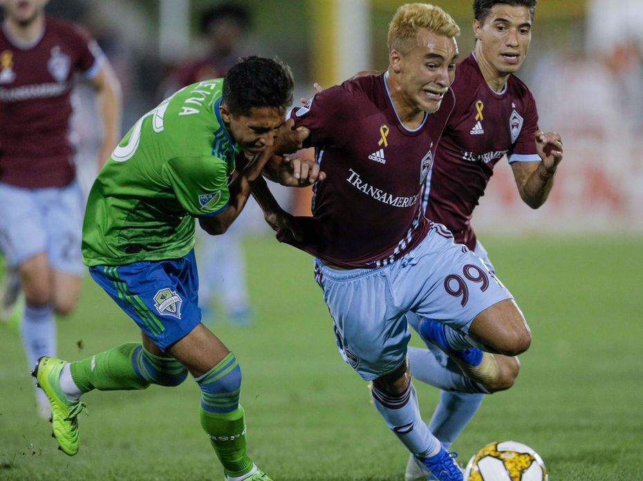 Seattle Sounders' Danny Leyva, left, tangles with Colorado Rapids' Andre Shinyashiki (99) during the second half of an MLS soccer match Saturday, Sept. 7, 2019, in Commerce City, Colo. Colorado won 2-0. (AP Photo/Joe Mahoney)