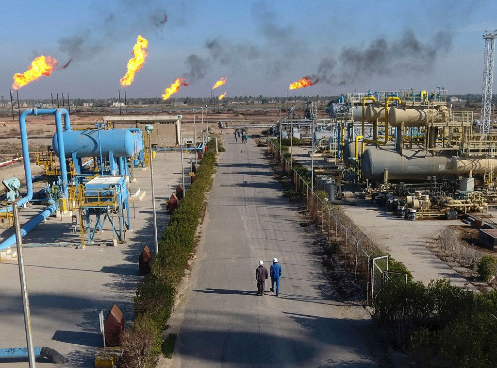 Laborers walk down a path in the Nihran Bin Omar field north of Basra, Iraq, 340 miles (550 kilometers) southeast of Baghdad, on Thursday, Jan. 12, 2017. Iraq's state-run South Gas Company inaugurated a gas pipeline to transport gas, a by-product of oil production, from Nihran Bin Omar field to the national network. (AP Photo/Nabil al-Jurani)