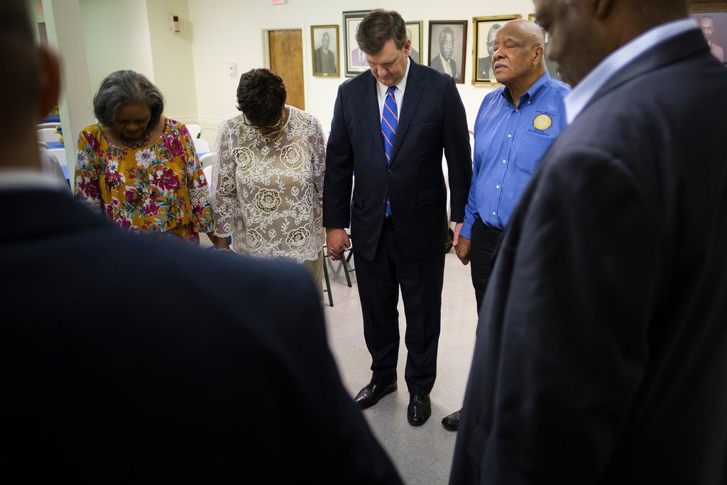 Dallas Mayor Mike Rawlings (center) holds hand is Patria Henderson Meshack (second from left) as he prays with members at St. Paul AME Church before services on Sunday, May 19, 2019, in Dallas. (Smiley N. Pool/The Dallas Morning News)