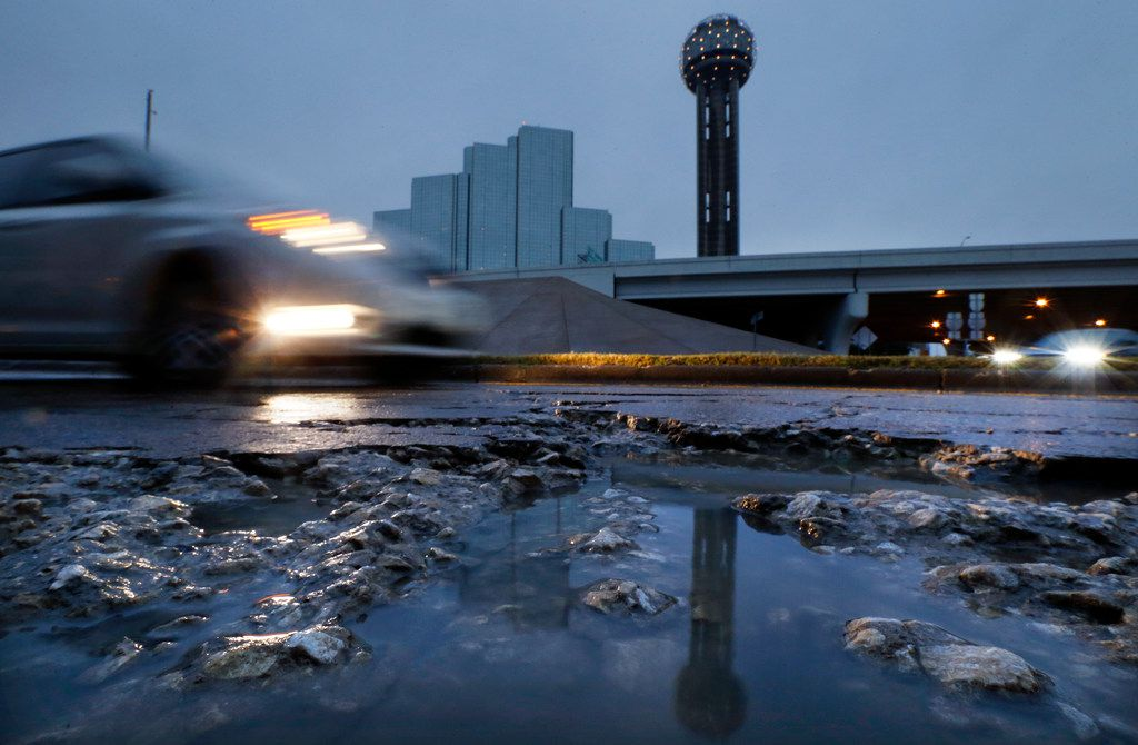 Reunion Tower is reflected in a rainwater-filled pothole near Reunion Boulevard in downtown Dallas on Jan. 2, 2019.
