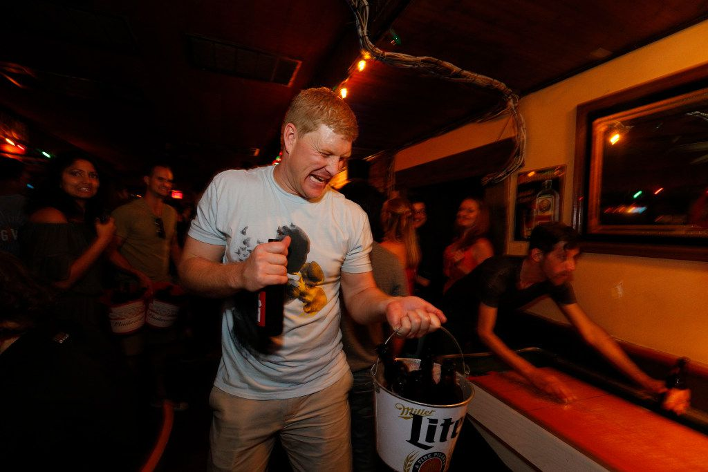 Kevin Weidlich Hands out beers during the last hours of operation of the Elbow Room in Dallas on April 16, 2017. (Nathan Hunsinger/The Dallas Morning News)