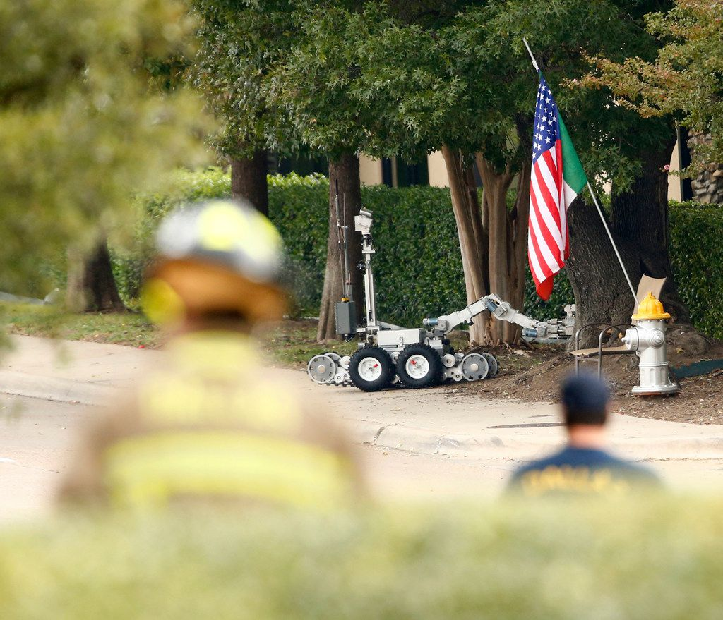 A suspicious package is pulled out of the bushes by a police robot in front of the Southwestern Women's Surgery center on Greenville in Dallas on Oct. 20, 2017. (Nathan Hunsinger/The Dallas Morning News)