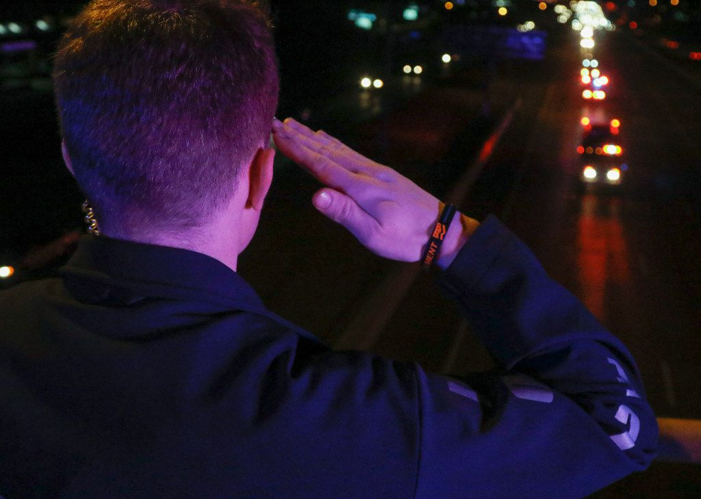 Richardson police Officer K. Collins stood at attention as the body of Richardson Officer David Sherrard was escorted in a motorcade to Restland Funeral Home in Dallas from the Collin County medical examiner's office in McKinney in February.