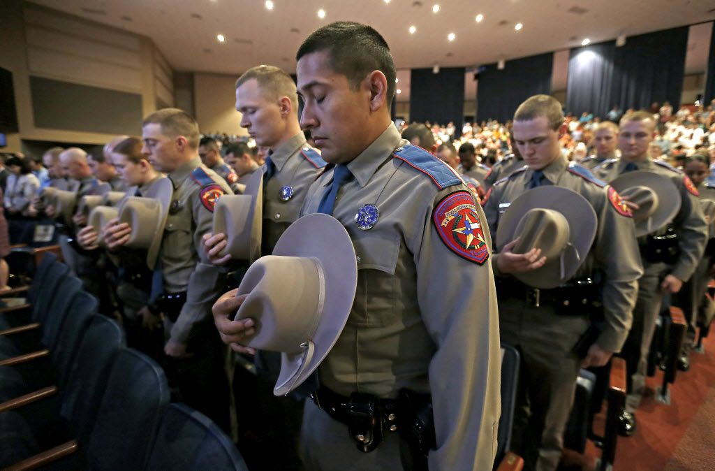 Members of the 155th trooper training class bow their heads during the Texas Department of Public Safety graduation ceremony at Shoreline Church on Friday, June 17, 2016, in Austin, Texas. DPS has the highest number of Hispanic trooper graduates at any time over the last decade and currently the classes of this year are about 40 percent Hispanic.