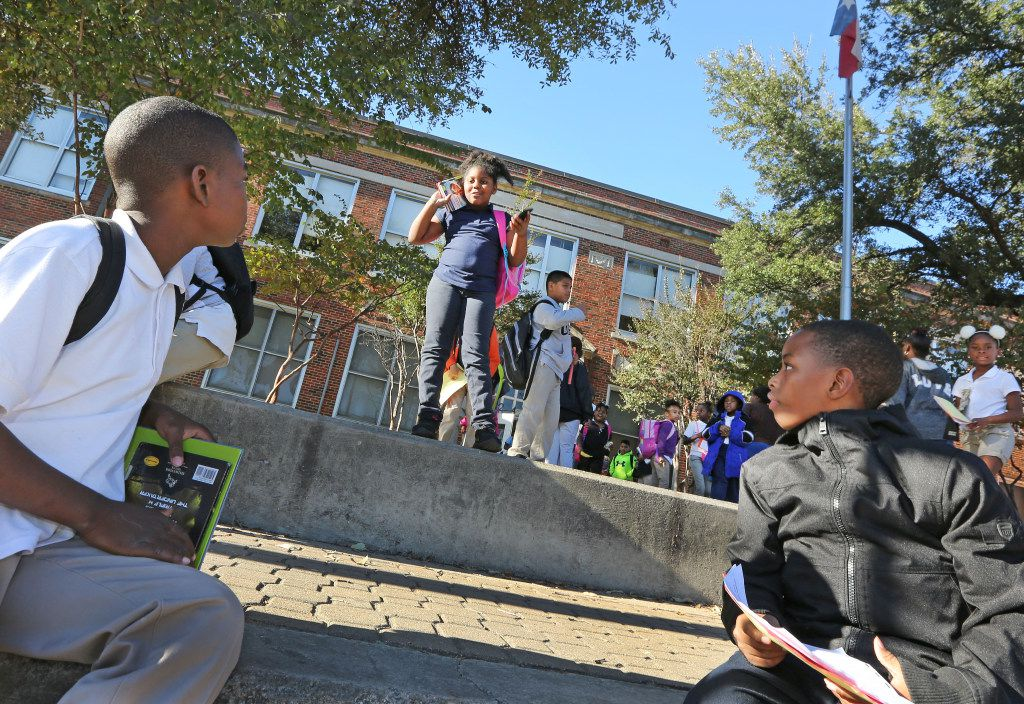 Student Tarueanna Standard, center, heads home as students get out of school at the Charles Rice Learning Center on Pine Street in Dallas on Wednesday, November 29, 2016. (Louis DeLuca/The Dallas Morning News)