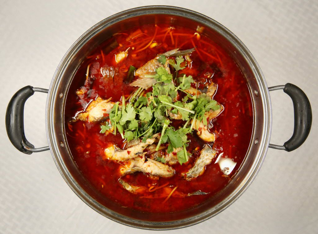 """A fish hot pot is one of the """"live fish"""" house specials that makes use of the tilapia that swim in the tanks along one wall."""