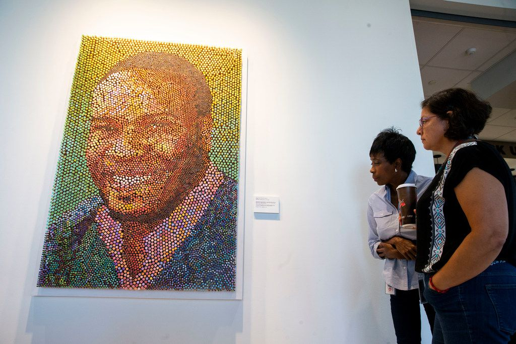 """Veta Christman, left, whispers """"I've never seen anything like it"""" to coworker Leticia Espinoza as they admire the artwork of Botham Jean."""
