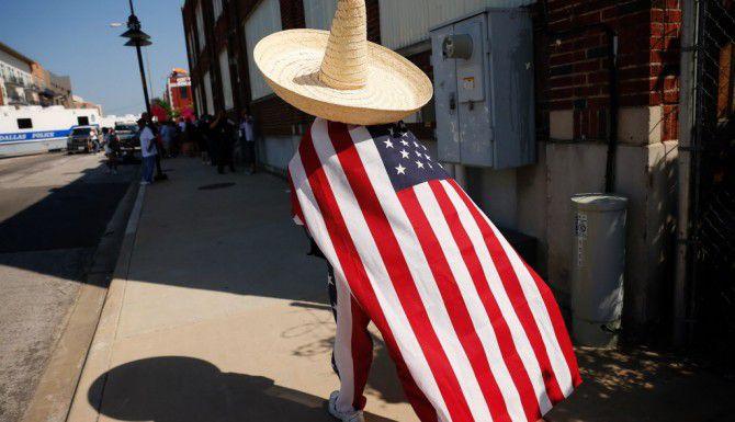 Julio Arellano camina por la calle Lamar para unirse a los manifestantes antes del rally del candidato presidencial Donald Trump en Dallas./ (G.J. McCarthy/The Dallas Morning News)