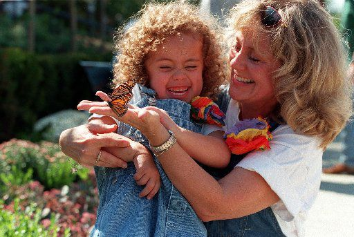 Amy Powell shows her granddaughter Ashton  Powell, 4, two of the over 1.200 butterflies released at the  Dallas Arboretum in October, 1997. (Staff Photo)