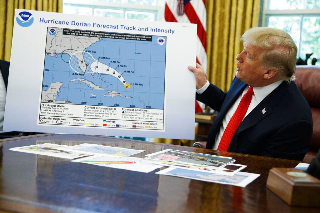 El presidente Donald Trump sostiene un mapa mientras hace declaraciones a la prensa después de que le informaran sobre el huracán Dorian, en la Oficina Oval de la Casa Blanca en Washington, el miércoles 4 de septiembre de 2019.