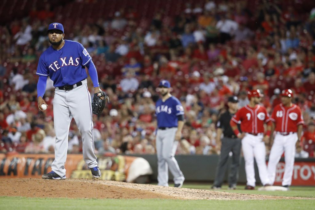 Texas Rangers relief pitcher Jeremy Jeffress, left, prepares to throw after walking Cincinnati Reds' Eugenio Suarez (7) during the seventh inning of a baseball game, Tuesday, Aug. 23, 2016, in Cincinnati. The Reds won 3-0. (AP Photo/John Minchillo)