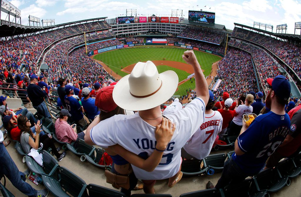 Texas Rangers and Michael Young fan Andrew Brown and his wife Andrea of Plano cheer during Opening Day player introductions at Globe Life Park in Arlington, Texas, Thursday, March 29, 2018. (Tom Fox/The Dallas Morning News)